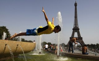 A young man jumps in a fountain of the Trocadero to cool off, in front of the Eiffel tower in Paris, August 19, 2012, as an unusual heatwave continues to hit continental Europe. REUTERS/Vincent Kessler (FRANCE - Tags: SOCIETY ENVIRONMENT TPX IMAGES OF THE DAY)
