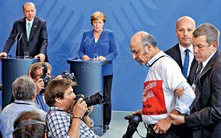 Ακτιβιστής απομακρύνεται υπό τα βλέμματα του Τούρκου προέδρου Ταγίπ Ερντογάν και της καγκελαρίου Αγκελα Μέρκελ. Επεισοδιακή ήταν η κοινή συνέντευξη Τύπου των δύο ηγετών, κατά την οποία ο Ερντογάν επιδίωξε την κατάργηση βίζας για τους Τούρκους υπηκόους και την προσέλκυση γερμανικών επενδύσεων. Εκδηλες, πάντως, ήταν οι διαφορές μεταξύ των δύο κρατών σε θέματα ανθρωπίνων δικαιωμάτων και τρομοκρατίας.