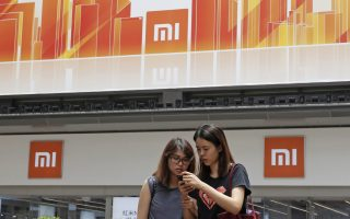 In this Wednesday, June 20, 2018, photo, people use their smartphone outside a Xiaomi store in Hong Kong. Xiaomi, a Chinese startup that helped to pioneer the trend toward ultra-low-priced smartphones, is preparing for what would be the biggest initial public offering since e-commerce giant Alibaba's in 2014. The 8-year-old is a star among the Chinese unicorns, a term that refers to startup companies that are valued at more than $1 billion. It has a dedicated Chinese fan base and its media-savvy leader is an Asian celebrity. But it is untested outside the region. (AP Photo/Kin Cheung)