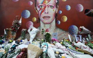 epa05097191 Flowers at a tribute mural for British singer David Bowie in Brixton, birth place of the late David Bowie in London, Britain, 11 January 2016.  Well-wishers have flocked to the Bowie mural to pay their respects following the announcement of his death.  EPA/ANDY RAIN
