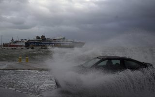 A car drives through seawater from crashing waves on the road during bad weather at the port of Rafina, east of Athens, on Thursday, Sept. 27, 2018. Severe weather warnings remain in effect around Greece, halting ferry services and prompting school closures. (AP Photo/Thanassis Stavrakis)