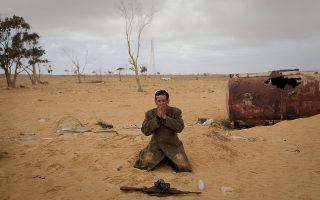 A Libyan rebel prays next to his gun on the frontline of the outskirts of the city of Ajdabiya, south of Benghazi, eastern Libya, Monday, March 21, 2011. The international military intervention in Libya is likely to last