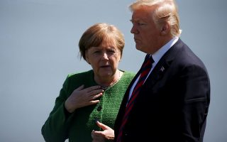 FILE PHOTO: Germany's Chancellor Angela Merkel talks with U.S. President Donald Trump during a family photo at the G7 Summit in Charlevoix, Quebec, Canada, June 8, 2018. REUTERS/Leah Millis/File Photo