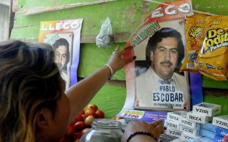 epa03351435 A woman puts in the wall a poster of a sticker collection of late Colombian drug lord Pablo Escobar in a slum in Medellin, Colombia, 08 August 2012. The stickers are being sold following the succes of a television program on Escobar in Colombia. Authorities announced they will be seizing the stickers following their ban.  EPA/Luis Eduardo Noriega