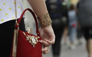 A woman holds her purse as she walks down an avenue during the 2018 soccer World Cup in St. Petersburg, Russia, Wednesday, July 11, 2018. (AP Photo/Petr David Josek)