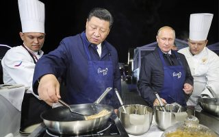 Chinese President Xi Jinping, second left, and Russian President Vladimir Putin, second right, prepare food, as they visit an exhibition during the Eastern Economic Forum in Vladivostok, Russia, Tuesday, Sept. 11, 2018. (Sergei Bobylev/TASS News Agency Pool Photo via AP)