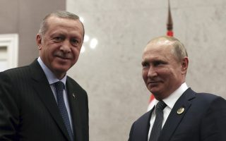 Turkey's President Recep Tayyip Erdogan, left, and Russian President Vladimir Putin shake hands prior to their meeting in Johannesburg, South Africa, Thursday, July 26, 2018. Erdogan and Putin are in the country to attend an emerging national economies summit (BRICS) in Johannesburg. (Presidential Press Service via AP, Pool)