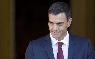 Spain's Prime Minister Pedro Sanchez steps out of the Moncloa Palace in Madrid, Spain, Wednesday, Sept. 12, 2018. Sanchez, who became prime minister in June promising to root out corruption, lost a culture minister over a tax fine and Spain's health minister resigned Tuesday over irregularities found in her master's degree. His center-left government has been marred by erratic policy-making, with several U-turns on cabinet decisions. (AP Photo/Paul White)