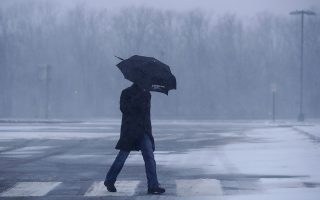 A man shields himself from gusty winds as snow falls on him at the Cheesequake Service Station along the Garden State Parkway during a snowstorm, Thursday, Jan. 4, 2018, in South Amboy, N.J. The New Jersey Shore, which has been experiencing deep cold weather to start the new year, is under a winter storm advisory. (AP Photo/Julio Cortez)