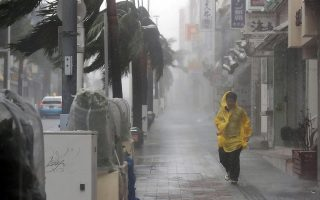A passer-by walks in heavy rain and wind caused by Typhoon Trami in the prefectural capital Naha, on the southern island of Okinawa, in this photo taken by Kyodo September 29, 2018. Mandatory credit Kyodo/via REUTERS ATTENTION EDITORS - THIS IMAGE WAS PROVIDED BY A THIRD PARTY. MANDATORY CREDIT. JAPAN OUT. NO COMMERCIAL OR EDITORIAL SALES IN JAPAN.      TPX IMAGES OF THE DAY