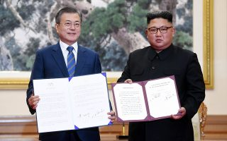 epaselect epa07031410 South Korean president Moon Jae-in (L) shows a document with North Korean leader Kim Jong-un (R) after a signing ceremony in Pyongyang, North Korea, 19 September 2018.  The third Inter-Korean summit takes place from 18 to 20 September in Pyongyang between South Korean President Moon Jae-in and North Korean leader Kim Jong-un.  EPA/PYONGYANG PRESS CORPS / POOL