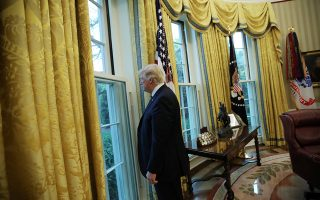 FILE PHOTO: U.S. President Donald Trump looks out a window of the Oval Office following an interview with Reuters at the White House in Washington, U.S., April 27, 2017. REUTERS/Carlos Barria/File Photo