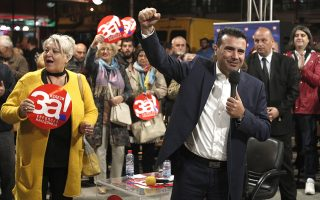 Macedonian Prime Minister Zoran Zaev, right, raises his fist while talking on the final pre-referendum rally of the coalition
