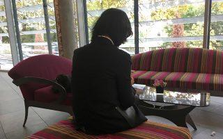 Η σύζυγος του προέδρου της Ιντερπόλ, με το πρόσωπο κρυμμένο, κοιτάει το κινητό της σε ξενοδοχείο της Λυών.