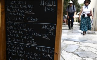 A board featuring menu prices of a tavern is seen at a narrow street of the central touristic Plaka area in Athens August 6, 2009. All over Europe the peak summer season looks equally bleak on low arrivals and even lower revenues as those who travel come on a budget, dragging countries like Greece, Spain and Italy, where tourism is a crucial source of income, deeper into crisis. Picture taken August 6.  To match feature EUROPE-TOURISM/    REUTERS/Yiorgos Karahalis (GREECE TRAVEL BUSINESS) - oikon -