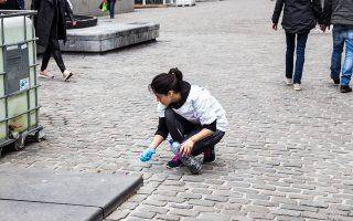 Μια κοπέλα μαζεύει γόπες από λιθόστρωτο στο κέντρο των Βρυξελλών.