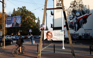 Ποδηλάτης μπροστά από προεκλογικές αφίσες στο Ρζαντιμίν της Πολωνίας.