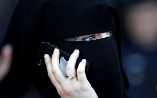 Γυναίκα με νικάμπ μιλάει στο τηλέφωνο έξω από γαλλικό δικαστήριο.