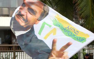 Υποστηρικτής του Ζαΐρ Μπολσονάρο πανηγυρίζει μπροστά από την κατοικία του, στο Ρίο ντε Τζανέιρο, τη νίκη του στις εκλογές της Κυριακής.