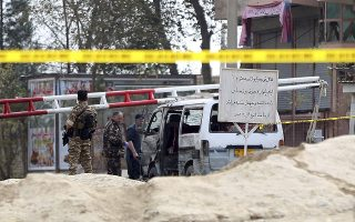 Security forces inspect the vehicle damaged by a suicide attack in Kabul, Afghanistan, Wednesday, Oct. 31, 2018. An Interior Ministry official says the suicide bomber has struck outside the country's largest prison on the eastern edge of the capital Kabul. (AP Photo/Massoud Hossaini)