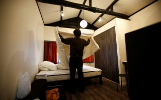 Yasuhiro Inaoka, who manages apartments for owners who provide short-term homestay lodging, arranges a bed after guests checked out at an apartment which is used as Airbnb service in Tokyo, Japan March 12, 2018. Picture taken March 12, 2018.  REUTERS/Kim Kyung-Hoon