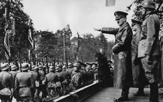 Ο ηγέτης του Τρίτου Ράιχ, Αδόλφος Χίτλερ, χαιρετάει τα παρελαύνοντα στρατεύματα της Βέρμαχτ, τα οποία διασχίζουν τους δρόμους της κατεχόμενης πλέον πολωνικής πρωτεύουσας με τον χαρακτηριστικό «βηματισμό της χήνας», μία εβδομάδα μετά την κατάληψη της πόλης από τα γερμανικά στρατεύματα, το 1939. Αυτή ήταν η πρώτη επίσκεψη του Χίτλερ στην κατεχόμενη Βαρσοβία, την πρώτη ευρωπαϊκή πρωτεύουσα που υπέκυψε στην εισβολή των ναζιστικών ορδών της Βέρμαχτ και των SS. (AP Photo)