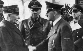 O καγκελάριος της Ναζιστικής Γερμανίας, Αδόλφος Χίτλερ, δίνει το χέρι του στον Γάλλο στρατάρχη Φιλίπ Πεταίν, επικεφαλής του φιλογερμανικού Κράτους του Βίσυ στο μη κατεχόμενο τμήμα της νότιας Γαλλίας, το 1940. Στα δεξιά βρίσκεται ο υπουργός Εξωτερικών της Γερμανίας, Γιοαχίμ φον Ρίμπεντροπ. (AP Photo)