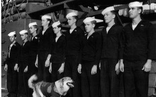 Μέλη του πληρώματος του αμερικανικού θωρηκτού «Νέα Υόρκη» στέκονται σε στάση προσοχής, καθώς πραγματοποιεί «επιθεώρηση» η μασκότ του πολεμικού πλοίου, μία σκυλίτσα που φέρει τον βαθμό του κελευστή, κατά την άφιξη της «Νέας Υόρκης» στο λιμάνι της ομώνυμης πόλης, το 1945. Το θωρηκτό υπήρξε το μοναδικό πλοίο των ΗΠΑ που συμμετείχε σε όλες τις φάσεις της Μάχης της Οκινάουα, στο μέτωπο του Ειρηνικού, βομβαρδίζοντας επί 78 ημέρες ιαπωνικές πολεμικές εγκαταστάσεις στις ακτές του νησιού. (AP Photo/Anthony Camerano)