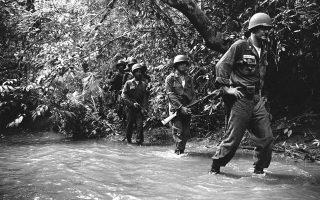 Ένας Αμερικανός στρατιωτικός σύμβουλος και Βιετναμέζοι στρατιώτες και αξιωματικοί πορεύονται σε μία βαλτώδη περιοχή της «πράσινης κόλασης» της βιετναμέζικης ζούγκλας, με τις φονικές παγίδες των Βιετκόνγκ να απειλούν ανά πάσα στιγμή τους άνδρες των στρατιωτικών δυνάμεων του Νότιου Βιετνάμ, κατά τη διάρκεια μίας αποστολής για την έρευση κρυμμένων κομμουνιστών ανταρτών, 40 χιλιόμετρα ανατολικά της Σαιγκόν, το 1962. (AP Photo/Horst Faas)