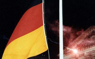 Παιδιά από την Ανατολική και τη Δυτική Γερμανία πραγματοποιούν την έπαρση της σημαίας της ενωμένης πλέον Γερμανίας, μπροστά από το κτίριο του Ράιχσταγκ στο Βερολίνο, το 1990. Στις 3 Οκτωβρίου του 1990 τέθηκε σε ισχύ η συνθήκη για την ενοποίηση των δύο Γερμανιών, έναν περίπου μήνα μετά την υπογραφή της, κλείνοντας οριστικά το ψυχροπολεμικό κεφάλαιο στην ιστορία της χώρας. (AP Photo/Hansjoerg Krauss)