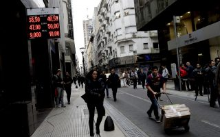 People walk past an exchange house in Buenos Aires, Argentina Thursday, Aug. 30, 2018. Argentina's Central Bank increased its benchmark interest rate to 60 percent Thursday as the peso hit a new all-time low. The sharp devaluation of its currency has led prompted Argentina to seek a financing deal with the International Monetary Fund. But the peso keeps tumbling and it has hit markets and investor confidence in Latin America's No. 3 economy.(AP Photo/Natacha Pisarenko)