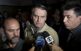 Presidential candidate Jair Bolsonaro, with the Social Liberal Party, talks to the press after visiting Federal Police headquarters in Rio de Janeiro, Brazil, Wednesday, Oct. 17, 2018. Bolsonaro won the first round of the presidential election Oct. 7 with 46 percent of the vote, but since he failed to top 50 percent, he is in a second-round ballot on Oct. 28. (AP Photo/Silvia Izquierdo)