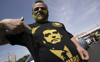 A demonstrator points his shirt with the image of the Jair Bolsonaro, presidential candidate for the National Social Liberal Party, during a race in the center of Brasilia, Brazil, Saturday, Oct. 6, 2018. Brazil will hold general elections on Oct. 7. (AP Photo/Eraldo Peres)