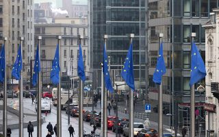 The British, right, and EU flags flap in the wind outside EU headquarters in Brussels on Monday, Dec. 4, 2017. British Prime Minister Theresa May and EU Commission President Jean-Claude Juncker will hold a power lunch on Monday, seeking a breakthrough in the Brexit negotiations ahead of a key EU summit the week after. (AP Photo/Virginia Mayo)