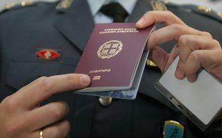Αξιωματικός της ΕΛΑΣ  επιδεικνύει διαβατήριο στο οπίο έχει εφαρμοστεί μικροτσίπ με   πληροφορίες ευαίσθητων προσωπικών δεδομένων πολίτη ,Υπηρεσία Διαβατηρίων , Αθήνα Τρίτη  29 Αυγούστου 2006.