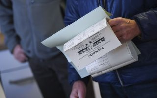 A man gets the ballot before casting his vote for the Hesse state elections at a polling station in Lich, Germany, Sunday, Oct. 28, 2018. (Arne Dedert/dpa via AP)