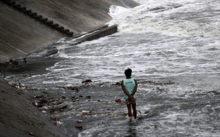 epa07019624 A Filipino villager is seen along a coastline  ahead of Typhoon Mangkhut landfall in the region, in the town of Aparri, Cagayan province, Philippines, 14 September 2018. Typhoon Mangkhut, ranked as the most powerful of the year to enter the Philippines braces for the arrival of the storm expected to hit the northern island of Luzon.  EPA/FRANCIS R. MALASIG