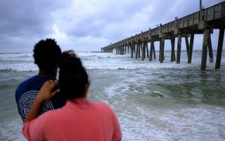 epa07081187 Eric O-neal (L) and his wife Mariana (R) watch the waves on the beach as Hurricane Michael approaches land in Pensacola, Florida, USA, 09 October 2018. Hurricane Michael has strengthened to a Category 2 hurricane and is expected to make landfall on the 09 October.  EPA/DAN ANDERSON