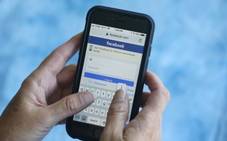 In this Tuesday, Aug. 21, 2018, photo a Facebook start page is shown on a smartphone in Surfside, Fla. (AP Photo/Wilfredo Lee)