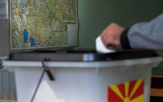 epa07059106 A map of The Former Yugoslav Republic of Macedonia (FYROM) in the background of a voting station during the referendum on the country's name change at a polling station in the town of Skopje, The Former Yugoslav Republic of Macedonia (FYROM), 30 September 2018. Almost two million Macedonians will vote in a national referendum on 30 September, on whether to change the country's name to 'North Macedonia' to endorse a name deal between FYR of Macedonia and Greece and to qualify for NATO membership.  EPA/NAKE BATEV