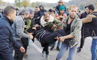 Μετανάστες μεταφέρουν μία από τους τραυματίες στα χθεσινά επεισόδια στα σύνορα Βοσνίας - Κροατίας.