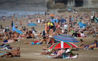 People sunbathe at Biarritz beach, southwestern France, Saturday, Oct.12, 2018. Temperatures in southwestern France have reached 30 degrees Celsius (86 Fahrenheit). (AP Photo/Bob Edme)