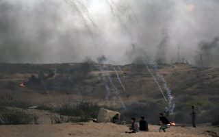 Tear gas canisters fired by Israeli troops fall over Palestinian protesters during a protest on the beach at the border with Israel near Beit Lahiya, northern Gaza Strip, Monday, Oct. 22, 2018. (AP Photo/Khalil Hamra)