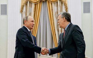 O Ρώσος πρόεδρος Βλαντιμίρ Πούτιν (αριστερά) ανταλλάσσει χειραψία με τον σύμβουλο Εθνικής Ασφαλείας του Λευκού Οίκου Τζον Μπόλτον, ο οποίος επισκέφθηκε τη Μόσχα την περασμένη Τρίτη.