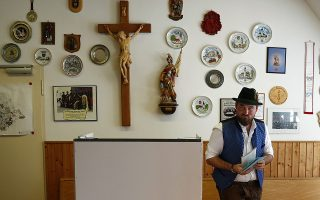 A young man in traditional Bavarian clothes casts his vote for the Bavarian state elections at a poling station in Maisach, southern Germany, Sunday, Oct. 14, 2018. (AP Photo/Matthias Schrader)