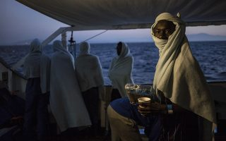 FILE - In this Thursday, Aug. 9, 2018 file photo, migrants stand on the deck of the Open Arms boat, after being rescued off the coast of Libya in the early hours of the night of Thursday, Aug. 2, 2018. The U.N. refugee agency says people smugglers are taking greater risks to ferry their human cargo toward Europe as Libya's coast guard increasingly intercepts boats carrying migrants, increasing the likelihood that those on board may die on the Mediterranean journey. That's one of the key findings from the latest UNHCR report about efforts to reach Europe. (AP Photo/Valerio Nicolosi, File)