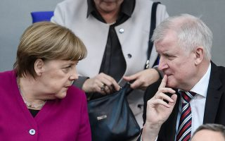 epa06618656 German Chancellor Angela Merkel (L) and the German Minister of Interior, Construction and Homeland, Horst Seehofer, talk prior to the Chancellor's speech to the German Bundestag in Berlin, Germany, 21 March 2018. Merkel, in her government declaration, spoke about the upcoming new German government's work.  EPA/CLEMENS BILAN