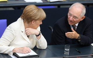 epa05412484 German Chancellor Angela Merkel (L) and Finance Minister Wolfgang Schauble (R) talk at the German Bundestag in Berlin, Germany, 07 July 2016. In her government declaration the Chancellor outlined the German strategy for the upcoming NATO summit.  EPA/WOLFGANG KUMM