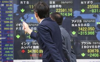 People look at an electronic stock board of a securities firm in Tokyo, Thursday, Oct. 11, 2018. Asian markets tumbled on Thursday, after Wall Street slumped on a heavy selling of technology and internet stocks. Japan's benchmark fell by an unusually wide margin of 3.9 percent. (AP Photo/Koji Sasahara)