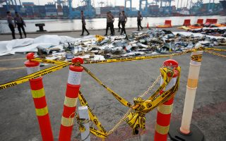 Police line is seen as Indonesian policemen walk near recovered debris and belongings of Lion Air flight JT610, that crashed into the sea, at Tanjung Priok port in Jakarta, Indonesia, October 31, 2018. REUTERS/Willy Kurniawan
